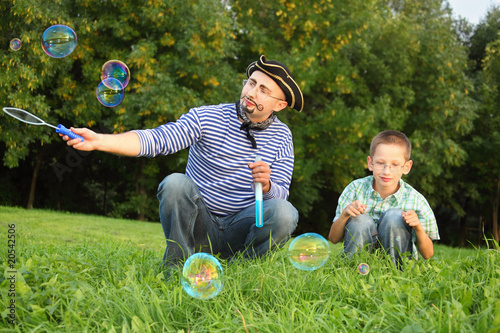 man with drawed beard is blowing soap bubbles. son is near