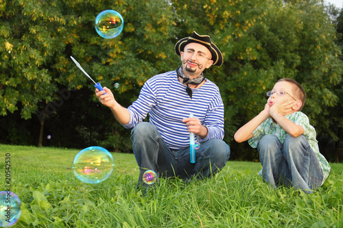 man with drawed beard and son is looking at onesoap bubble.