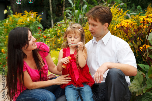 Little girl blows soap bubbles in summer garden with parents.