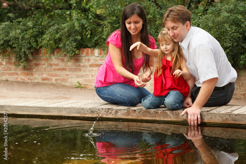 Little girl throws stones in water together with parents.