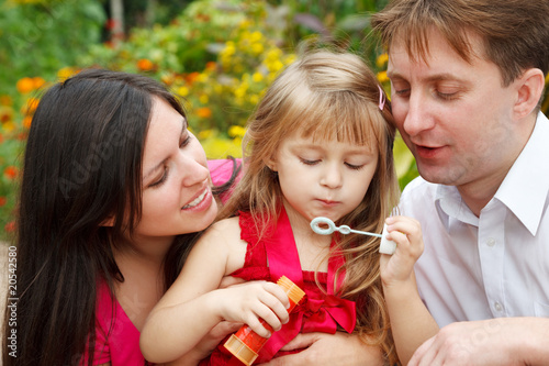Parents observe as daughter blows soap bubbles in summer garden