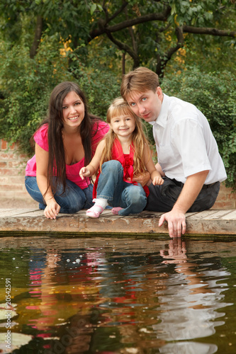 Little girl with parents sits on bank of reservoir in summer