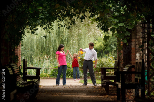 Girl plays being shaken on hands of parents in park