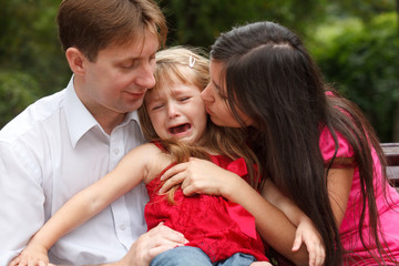 Parents calm crying girl on walk in summer garden