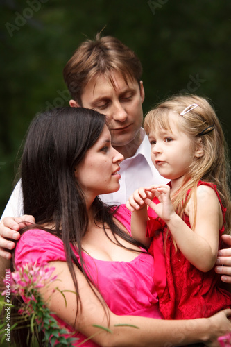 Young family in summer garden. Mum holds daughter on hands
