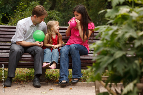 Parents together with daughter on bench in park in afternoon