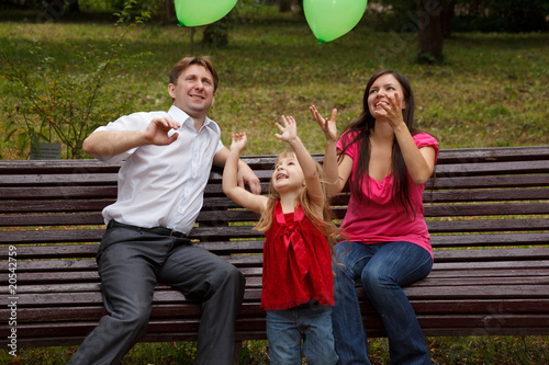 Parents with daughter on bench in park. Play with green balloon.