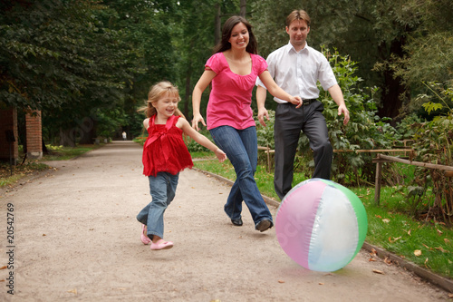 Little girl plays with big inflatable ball in park with parents.