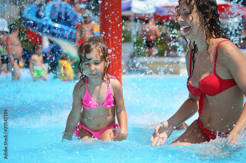 Smiling beautiful woman and little girl bathes in pool under wat