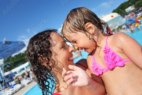 Smiling beautiful woman and little girl bathing in pool