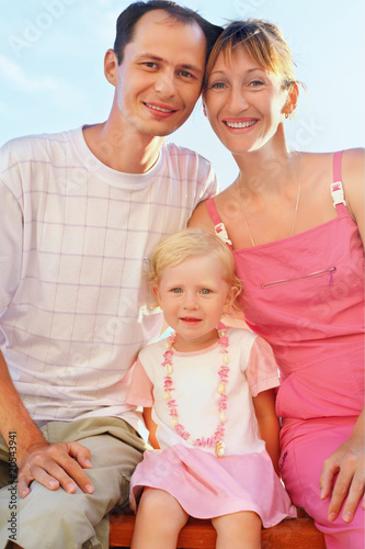 Happy family with little girl on beach