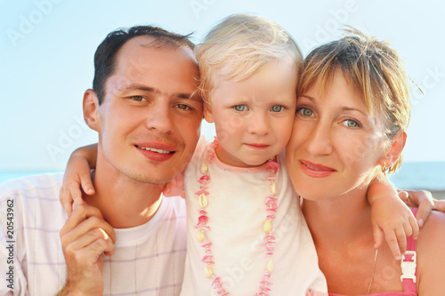 Happy family with little girl near to sea, concerning with heads