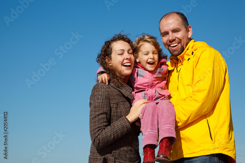 Happy parents together with daughter on hands bright sunny day
