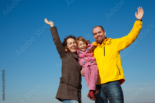 Happy parents with daughter with hands lifted upwards