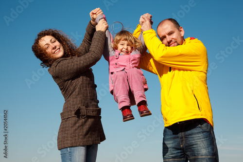 Happy girl shakes on hands at parents against blue sky