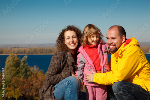 Little girl with mum and daddy, in bright autumn day