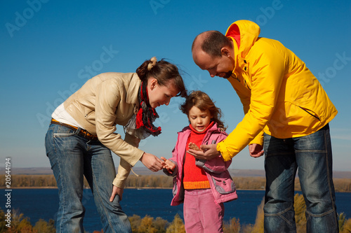 Little girl plays with parents nature in bright autumn day.