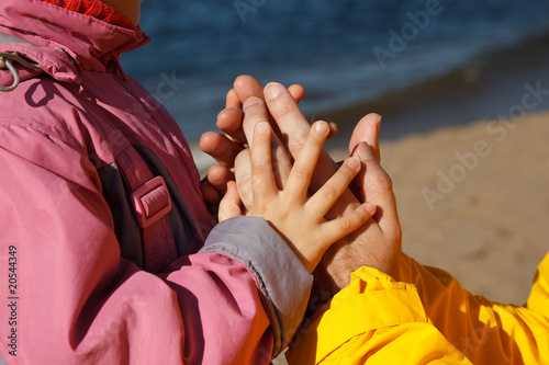 Child holds hand of adult. Photo close-up, on sunny autumn day.