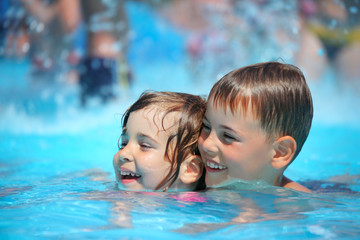 Smiling boy and little girl swimming in pool in aquapark
