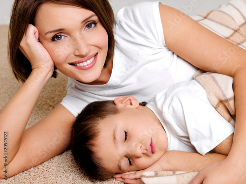 Portrait of the happy mother to the sleeping small son