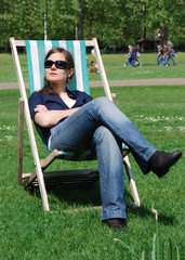 Young woman relaxing on a deck chair in Hyde Park, London