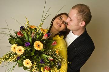 Junges verliebtes, glückliches Paar mit Blumenstrauß