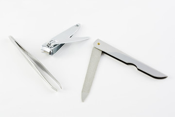 Nail cutter nail file and pincer over white background