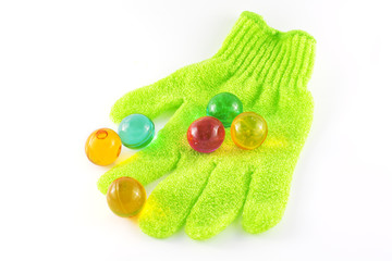 Bath glove with coloured bath pearls over white background