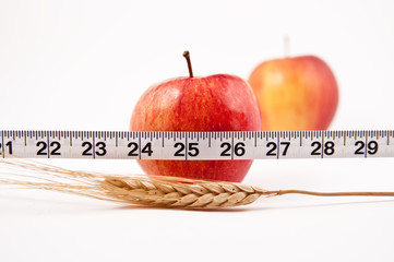 Two red Apples, one in focus behind a tape measure