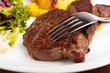 Gabel auf ein Steak mit Salat und Bratkartoffeln