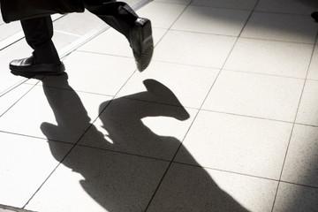 歩く男性の足と影
