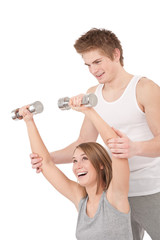 Fitness - Young woman with instructor lifting weights
