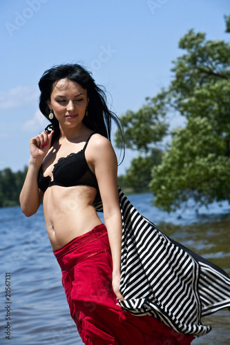 Beautiful young woman dreaming on the beach