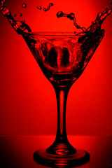 red glass of martini with splash