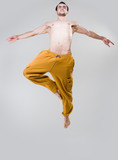 Young dancer jumping over gray background
