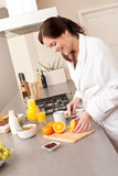 Young woman in bathrobe cutting orange in kitchen poster