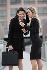 Two attractive women in business suits and skirts outside