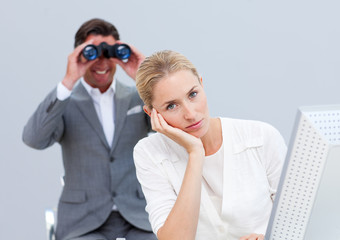 Blond businesswoman annoyed by a man looking through binoculars