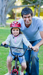 Cute little girl learning to ride a bike with her father