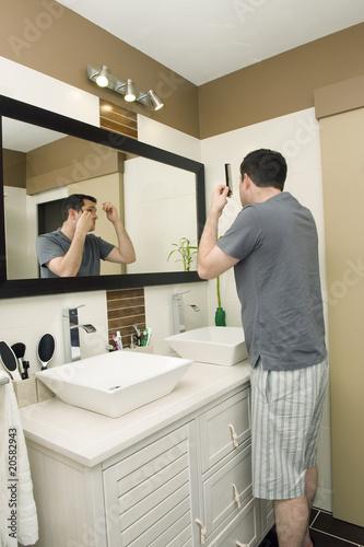 homme se coiffant dans sa salle de bain photo libre de droits sur la banque d 39 images fotolia. Black Bedroom Furniture Sets. Home Design Ideas