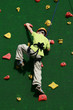 child climbing on a wall in an outdoor climbing center