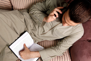 Male talking on phone while reading a book