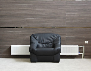 Alone black chair with radiator in minimalist interior
