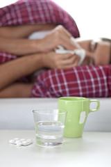 Tabletten und Tee neben erkälteter Person