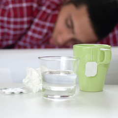 Tee, Tabletten und Glas Wasser vor kranker Person