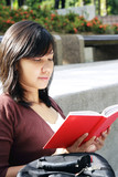 A young asian woman reading at a park