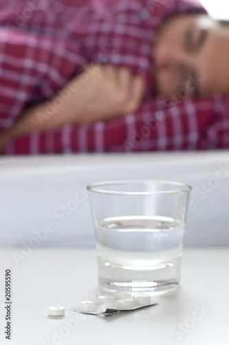 Tablets and glass of water next to a sleeping person