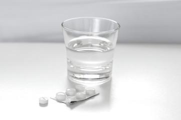 Tabletten neben Glas Wasser