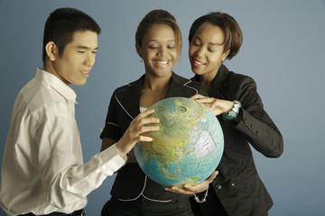 Gruppe hält einen Globus in der Hand