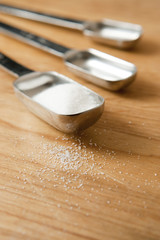 Measurings Spoons on Wood Counter with Sugar